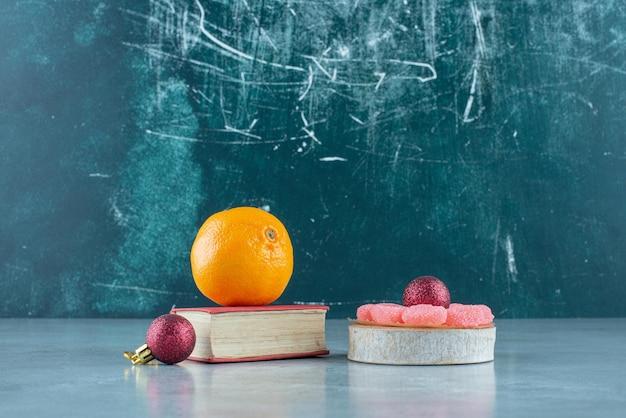 Naranja sobre libro, mermeladas sobre pieza de madera y dos bolas decorativas sobre mármol.