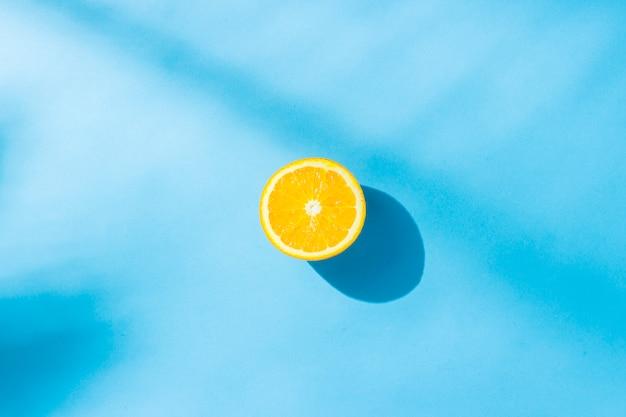 Naranja sobre una superficie azul bajo luz natural con sombras. luz dura. concepto de dieta, alimentación saludable, descanso en los trópicos, vacaciones y viajes, vitaminas. vista plana, vista superior.