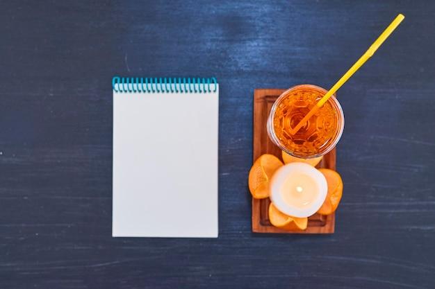 Naranja y un vaso de jugo con tubo amarillo en bandeja de madera con cuaderno blanco. foto de alta calidad