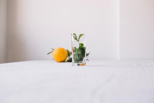 Naranja con vaso vacío en composición