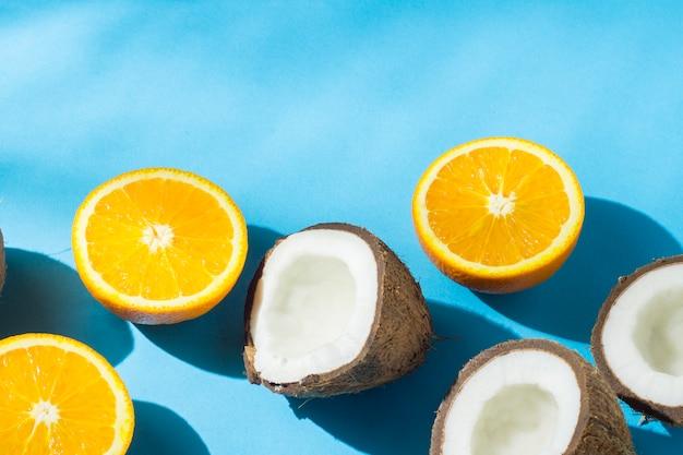Naranjas y coco sobre una superficie azul bajo luz natural con sombras. luz dura. concepto de dieta, alimentación saludable, vacaciones en los trópicos, vacaciones y viajes.