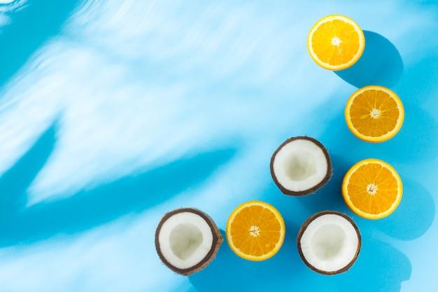 Naranjas y coco sobre una superficie azul bajo luz natural con sombras. vista plana, vista superior.