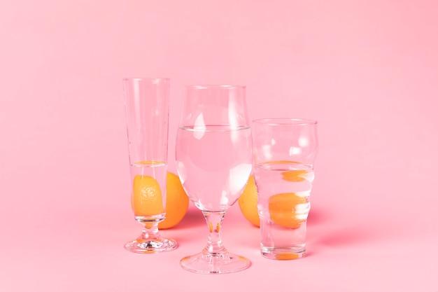 Naranjas detrás de vasos de agua.