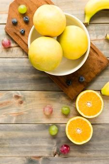 Naranjas enteras; uvas; plátano y arándanos sobre fondo de madera