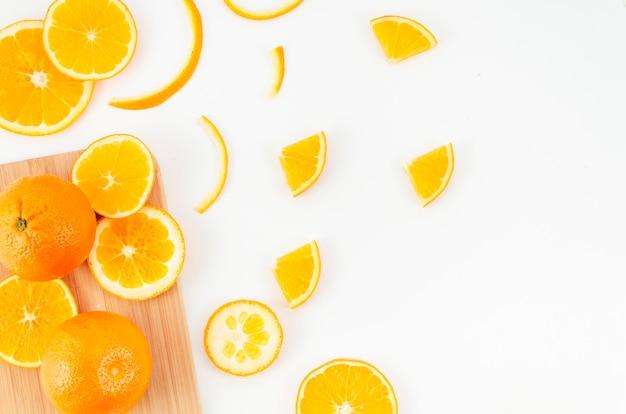 Naranjas esparcidas sobre tabla de cortar y mesa
