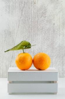 Naranjas frescas con la hoja en una caja de madera, vista lateral.