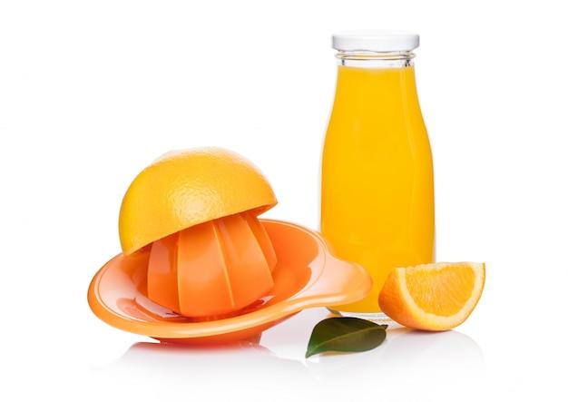Naranjas frescas peladas crudas con exprimidor de jugo y botella de vidrio con hojas sobre fondo blanco.