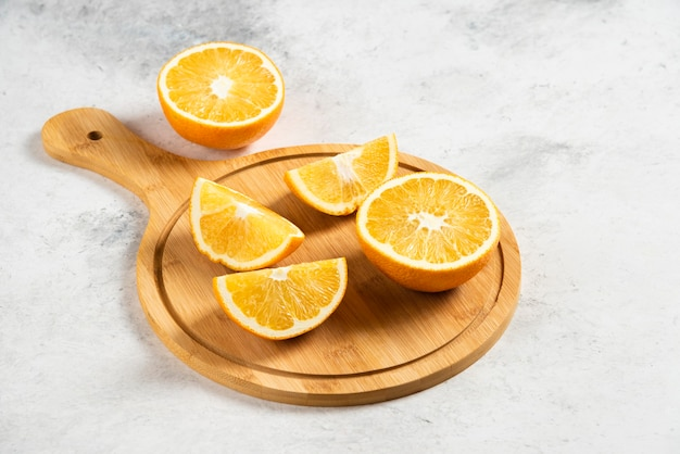 Naranjas frescas en rodajas con escariador de madera sobre mármol.