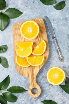 Naranjas frescas en rodajas en la tabla de cortar sobre superficie de hormigón