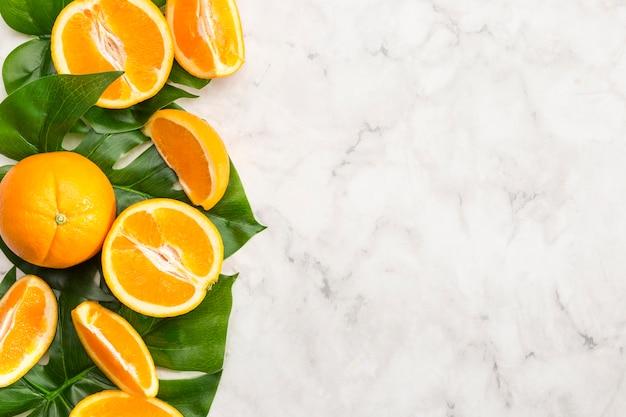 Naranjas y hojas de monstera sobre superficie de mármol
