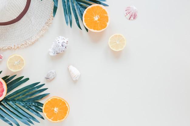 Naranjas con hojas de palmera, conchas y sombrero de paja.