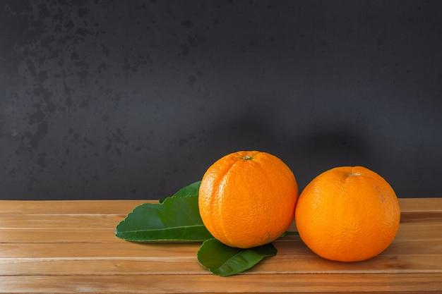 Naranjas y hojas verdes sobre piso de madera