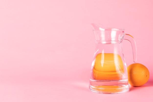 Naranjas y jarra de agua con espacio de copia