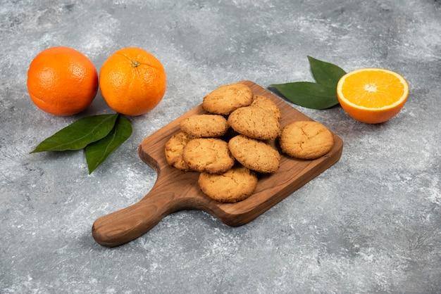 Naranjas orgánicas frescas enteras o cortadas y galletas caseras sobre tabla de madera.