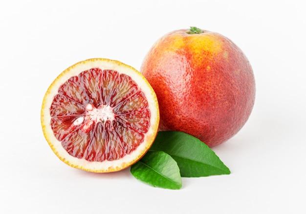 Naranjas rojas maduras frescas sobre fondo blanco.