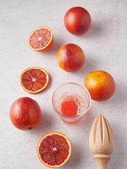 Naranjas sanguinas enteras y en rodajas listas para exprimir. exprimidor de vidrio y madera manual