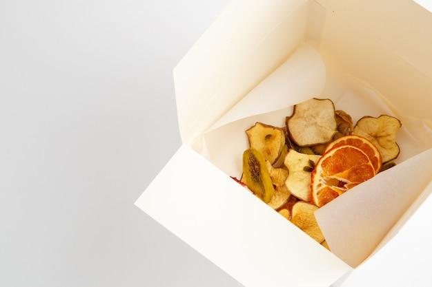 Naranjas secas, plátanos y manzanas en caja blanca sobre fondo blanco.