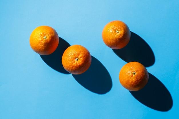 Naranjas sobre una superficie azul. luz dura. concepto de trópicos, comida sana, desayuno, dieta, vacaciones. vista plana, vista superior.