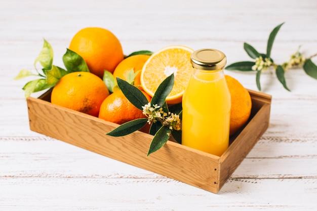 Naranjas y zumo en caja de madera.