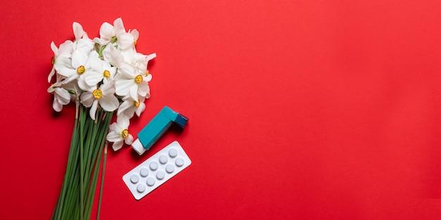 Narciso blanco con un fármaco farmacéutico inhalador para el asma azul