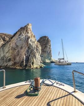 Nariz de un barco de yate dirigido a los acantilados en el mar egeo. santorini, grecia.