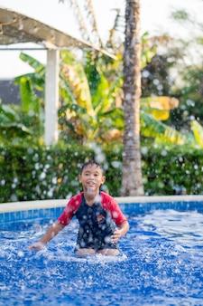 Natación asiática feliz del muchacho del niño en piscina en el verano