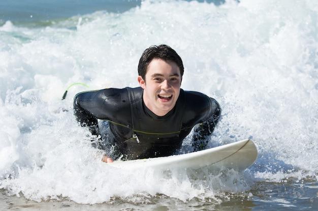 Natación feliz del hombre joven en la tabla hawaiana en el océano