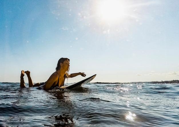 Natación de la mujer joven en la tabla hawaiana en agua
