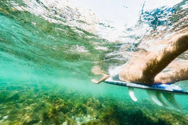 Natación de la mujer en la tabla hawaiana en el mar azul