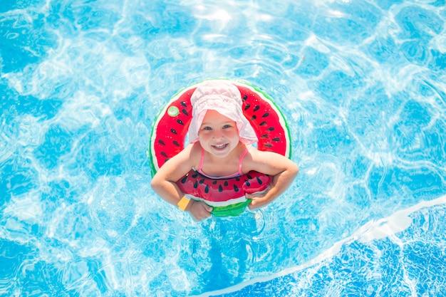 Natación, vacaciones de verano - niña sonriente encantadora en el sombrero rosado que juega en el agua azul con el espacio del salvavidas-sandía para el texto.