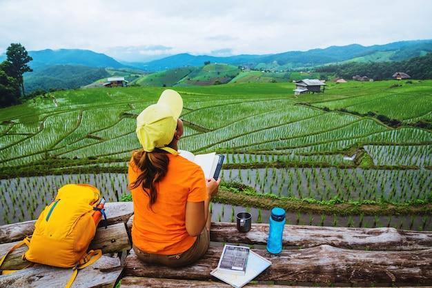 Naturaleza asiática del viaje de la mujer. viajar relajarse. libro de lectura de pie del balcón de la casa. en verano.