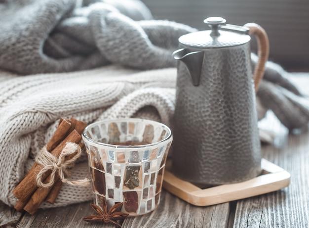 Naturaleza muerta con artículos de decoración para el hogar, teteras y un vaso de té en una mesa de madera en el interior de la sala de estar, concepto hogareño