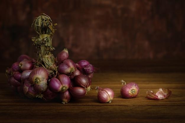 Naturaleza muerta con cebolla en rústica mesa de madera, elija un punto focal.