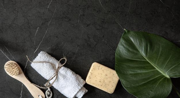 Naturaleza muerta con cepillo para el cuerpo, toalla y jabón en un espacio de copia de superficie de mármol oscuro. concepto de cuidado corporal.