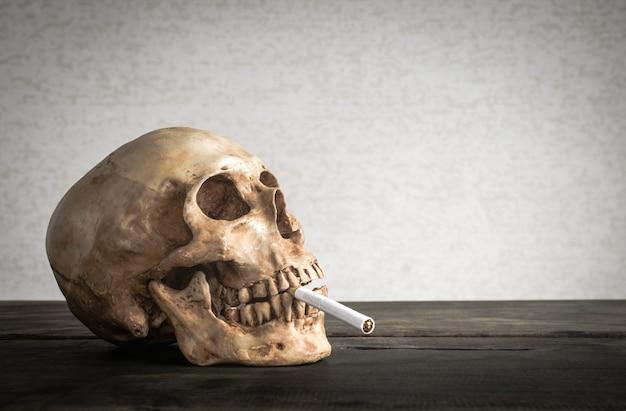 Naturaleza muerta cráneo de un esqueleto con cigarrillo encendido, deje de fumar concepto de campaña con espacio de copia.