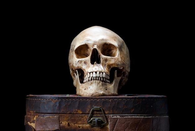 La naturaleza muerta con cráneo humano se coloca en una vieja caja de cuero aislada sobre fondo negro