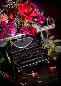 Naturaleza muerta: imprenta antigua y flores brillantes sobre un fondo oscuro.