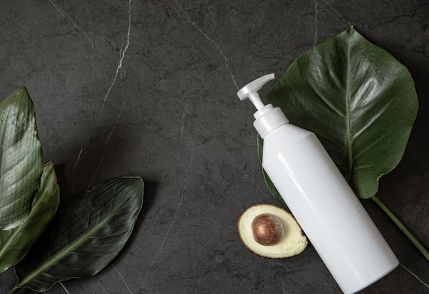 Naturaleza muerta con maqueta de botella dispensadora cosmética blanca con aguacate y vista superior de hojas. concepto de belleza e higiene.