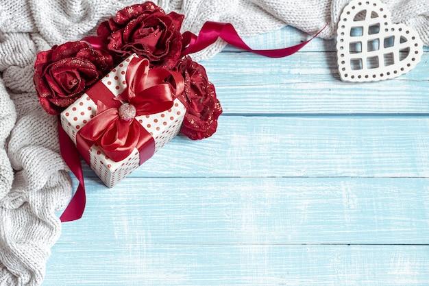 Naturaleza muerta con un regalo bellamente envuelto, flores y elementos decorativos sobre una superficie de madera. concepto de vacaciones de san valentín.