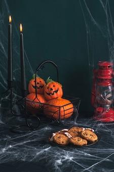 Naturaleza muerta sobre el tema de la fiesta de halloween. sobre la mesa hay una canasta de calabazas, dos velas negras, un plato de galletas. la mesa está enredada en telarañas.