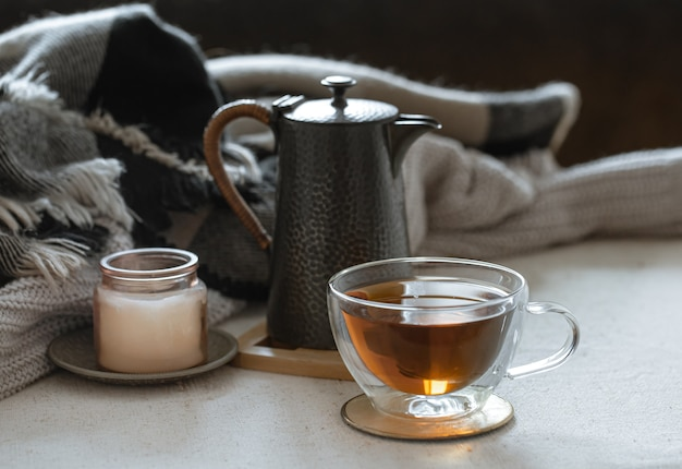 Naturaleza muerta con una taza de té, una tetera, un libro y detalles decorativos