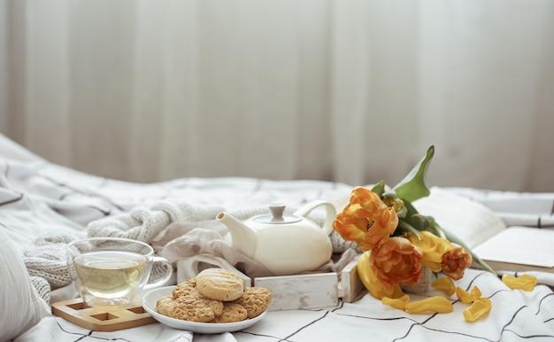 Naturaleza muerta con una taza de té, una tetera, un ramo de tulipanes y galletas en la cama