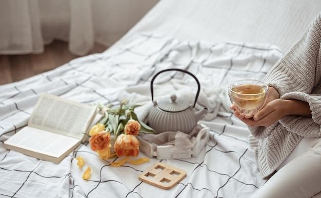 Naturaleza muerta con una taza de té, una tetera, un ramo de tulipanes y un libro en la cama