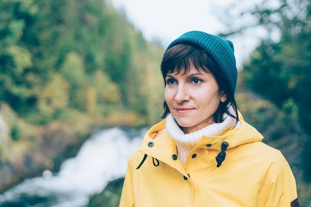Uno con la naturaleza. mujer mirando al bosque y cascada