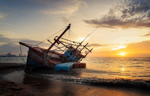 Naufragio abandonado de barco de pesca de madera en la playa Foto Premium