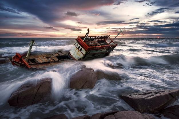 Naufragio barco abandonado stand en la playa de roca