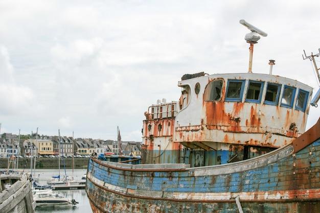 Naufragio oxidado amarrado, abandonado en el muelle en el puerto