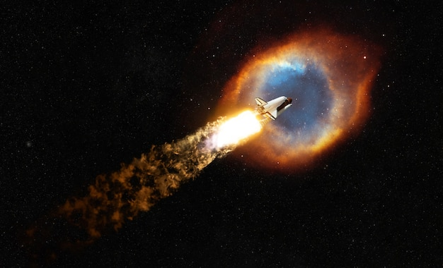 Nave espacial vuela en el espacio hacia la nebulosa coloreada. cohete espacial con explosión y bocanadas de humo despega y conquista el espacio exterior. concepto de viaje