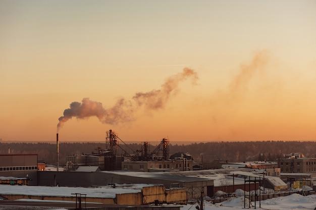 Naves industriales al amanecer. almacenes humo de la pipa. gradiente.
