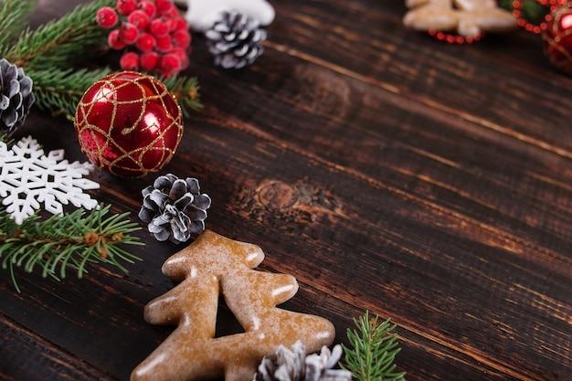 Navidad, abetos, adornos hechos a mano y galletas de jengibre en una mesa de madera, espacio de copia, vista superior.